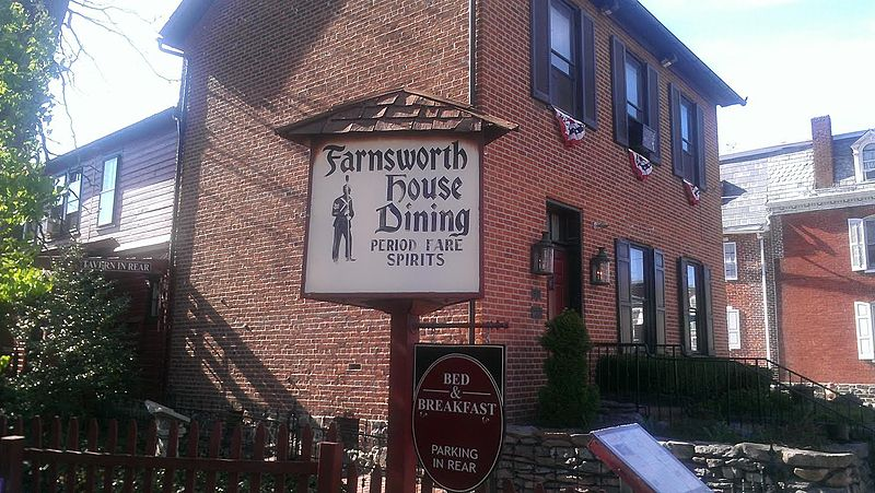 """photo shows the facade of the farnsworth house inn, with a sign that reads """"period fare spirits"""""""