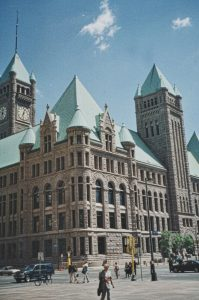photo shows the outside of the minneapolis city hall, with stained green towers and brown brick