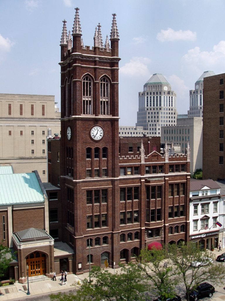 photo shows the christ church cathedral, which is a towering red brick structure with pointed spires and a large clock face.