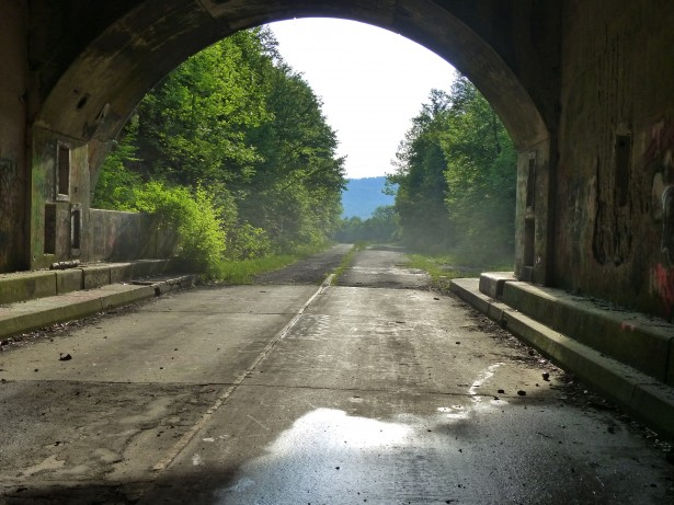 photo shows an abandoned road leading through a tunnel