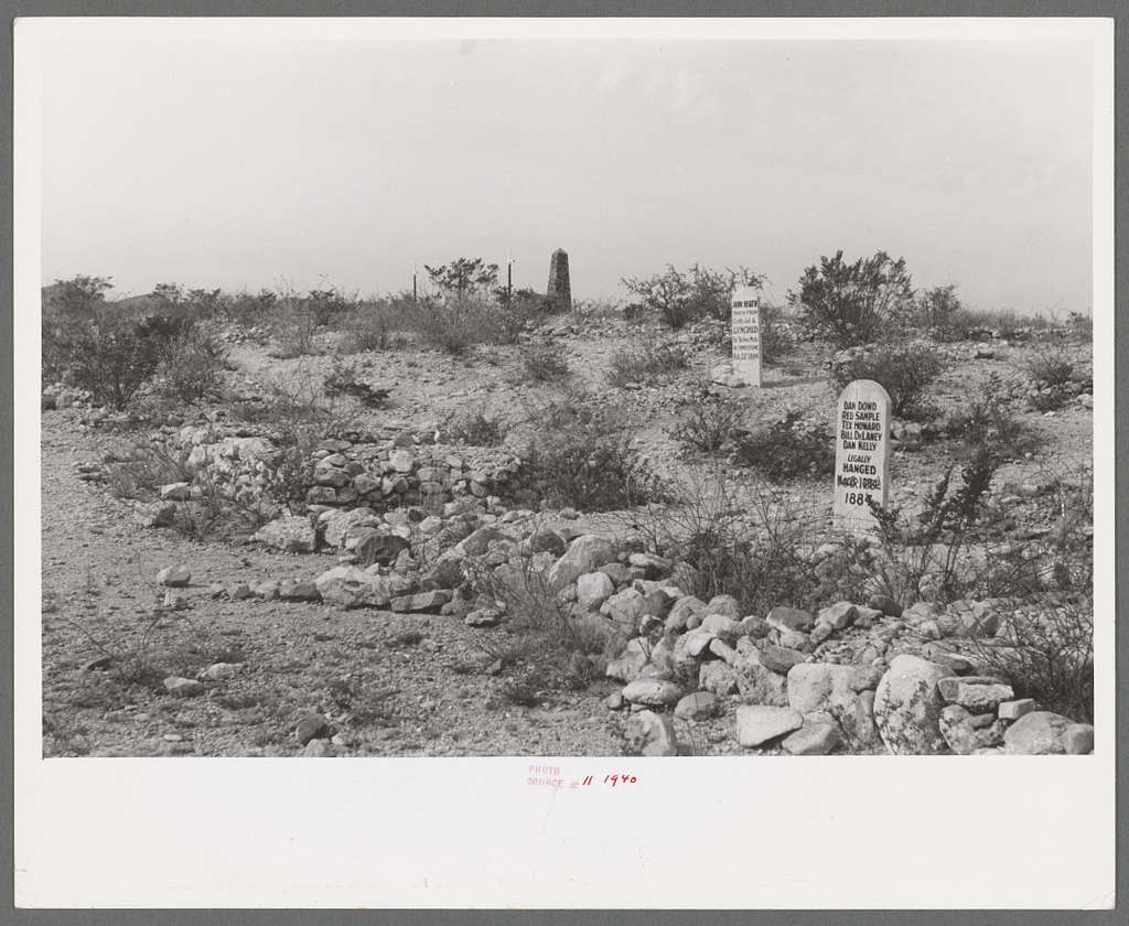 photo shows the landscape of foothill cemetery with some old tombstones and desert brush